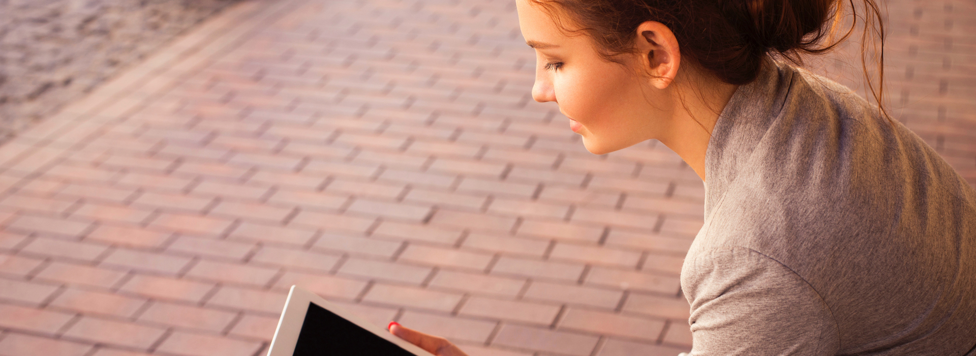 A woman sits outside, reading from a tablet.